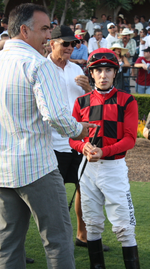 Bob Hess, Jr. talks strategy with jockey Michael Baze in the Del Mar paddock